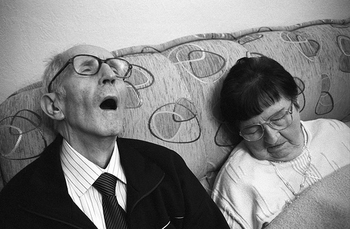 Elderly couple asleep on couch