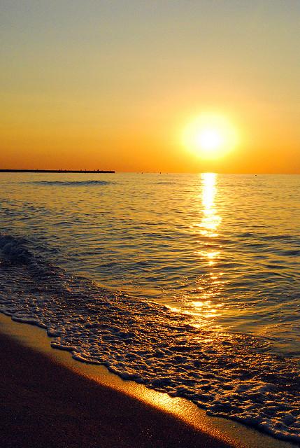 Sun over ocean sand